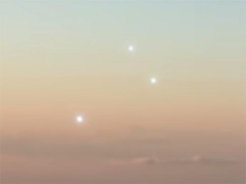 白く輝く3つの飛行物体が、旅客機と並んで飛行