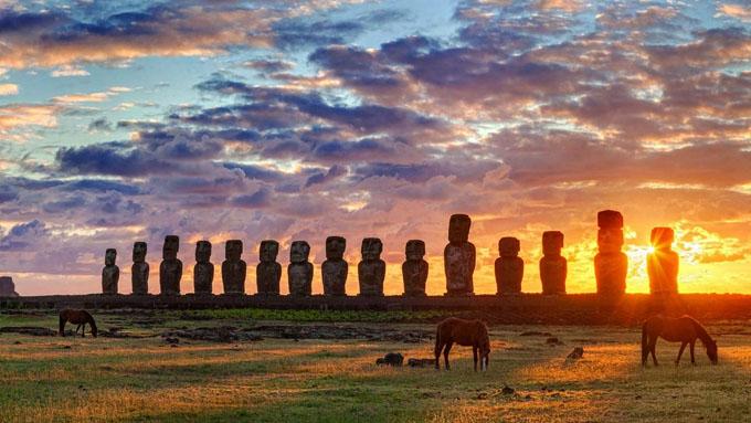 夕日を背景に立ち並ぶモアイ像