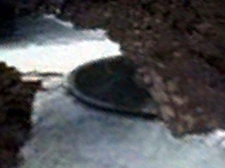 南極大陸の岩場の陰に、マンホールの蓋のような円盤型UFO! グーグルアースで発見される!